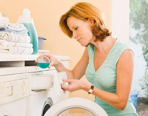 Женщина заливает кондиционер в машинку